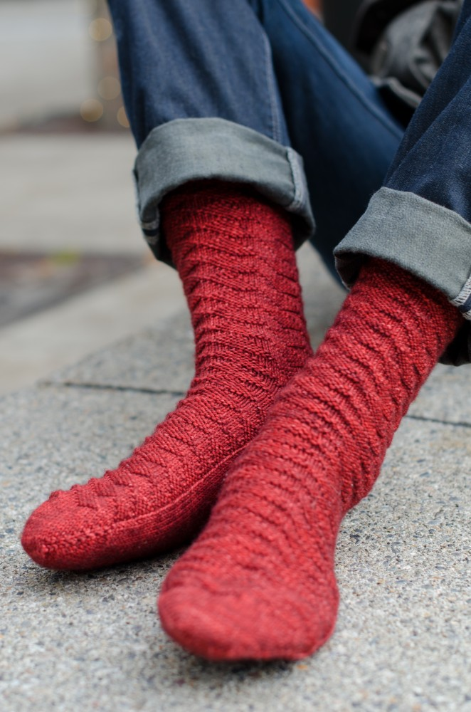 The geometric knit-and-purl stitch pattern is worked in DK weight yarn at a dense gauge, creating a durable and warm sock