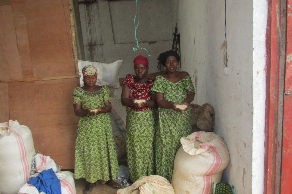 Three of the women pose with what rice they've managed to salvage from storage after the flooding. They lost nearly 2 tons. Photo by Prosper Ndabishuriye.